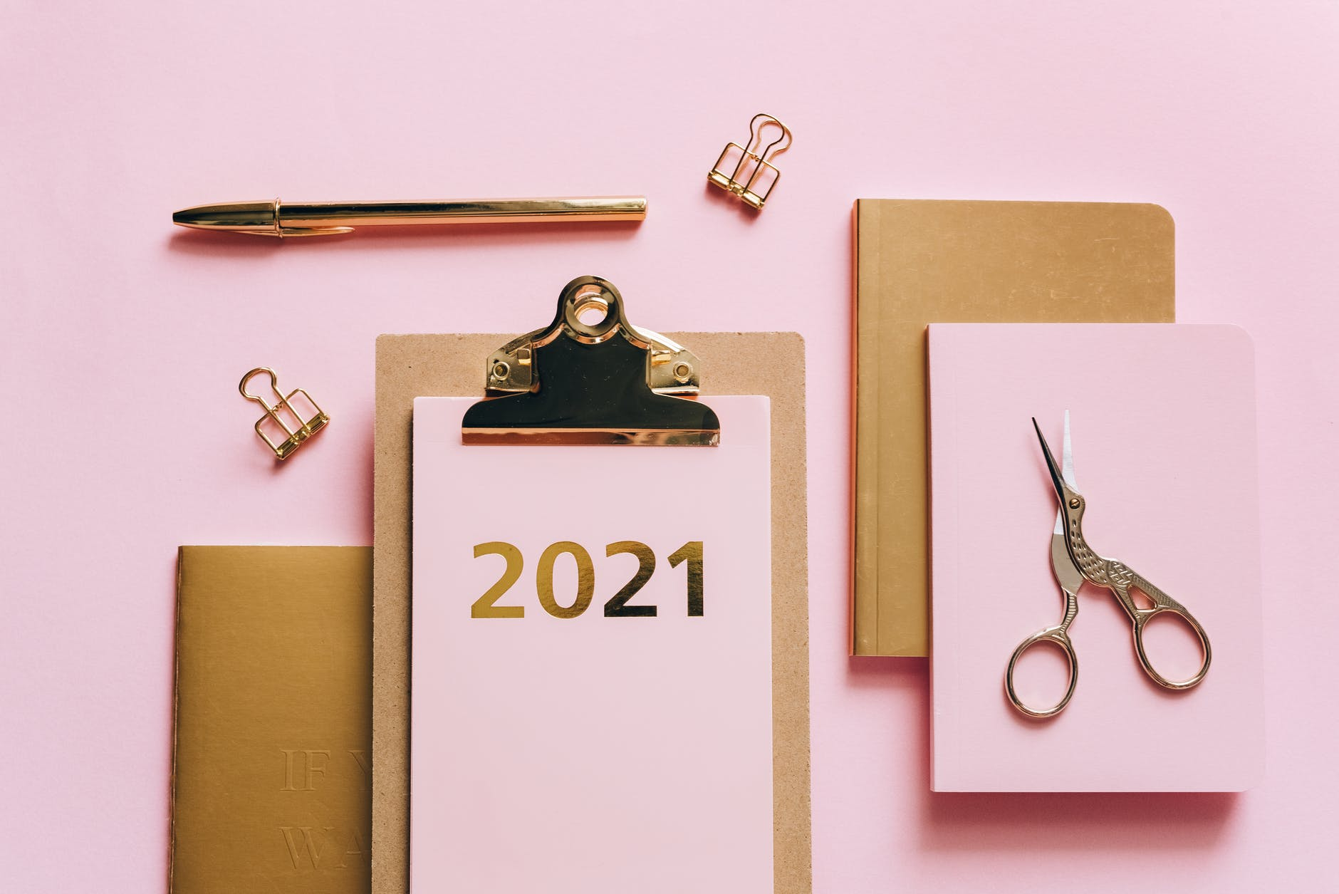 Photo of pale pink office supplies and planner for the year 2021.